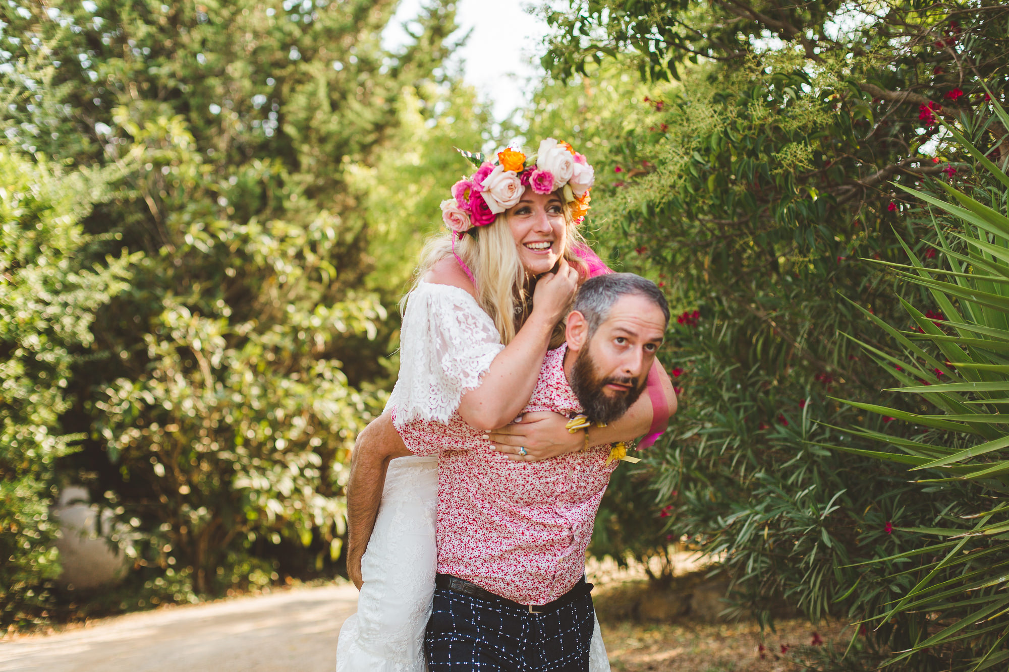 Groom giving bride a piggy back down the aisle at her beautiful destination wedding in France