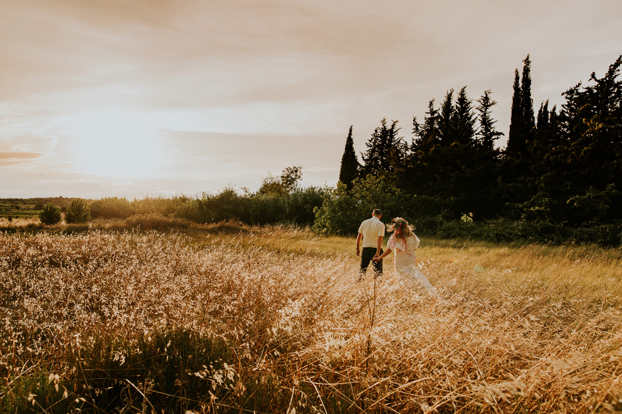 Bride and groom walking in a field on their wedding day in chateau du puits es pratx. What a beautiful destination wedding in France.