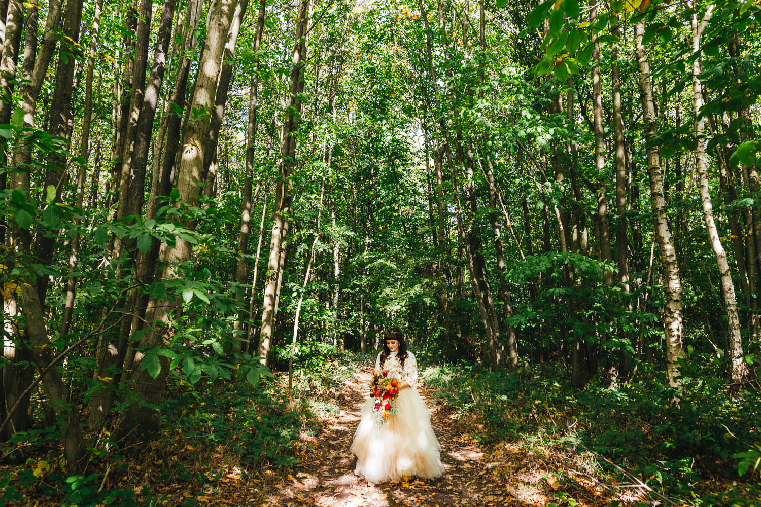 Image of bride in woodland taken by Quirky Fun Colourful Kent Wedding Photographer