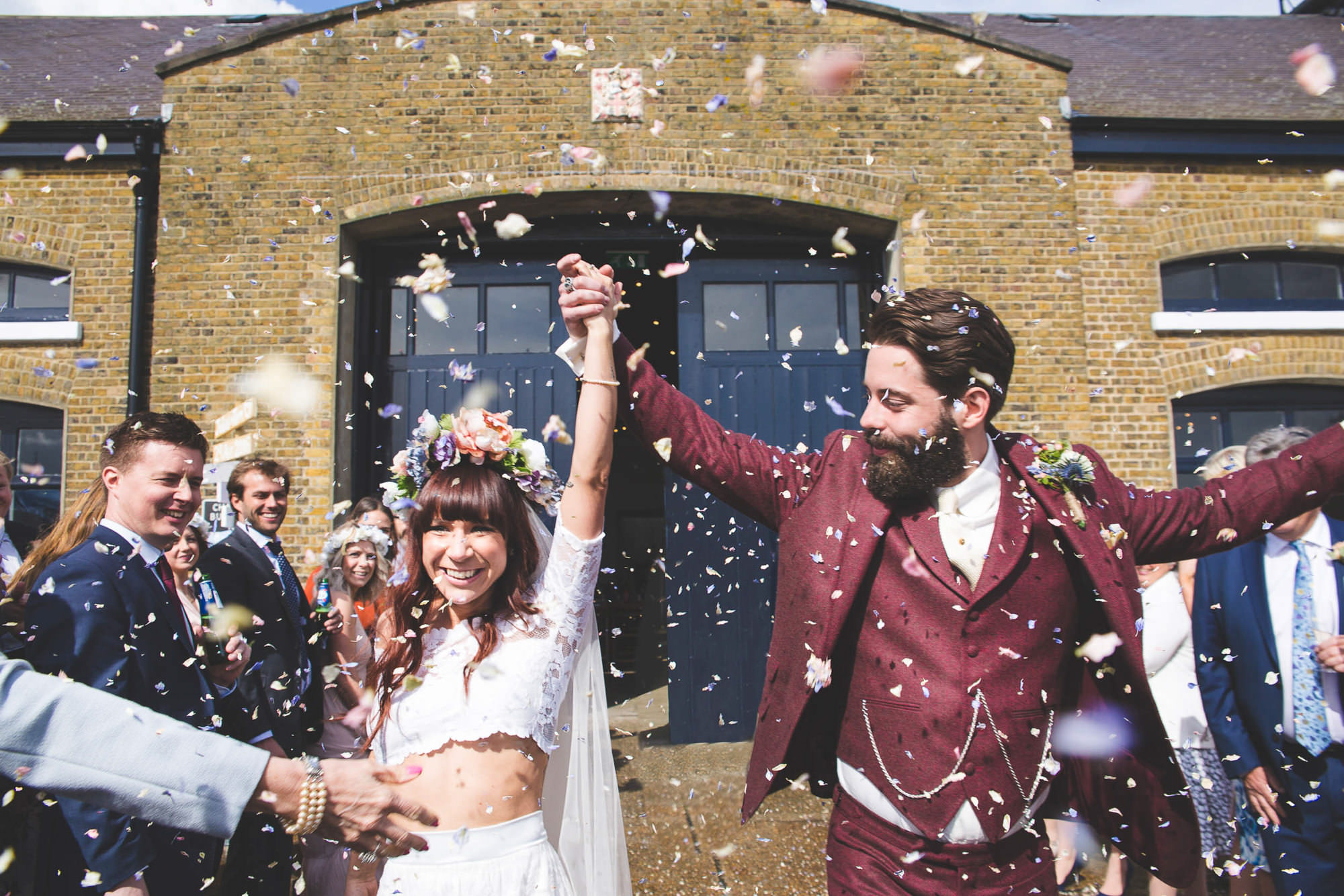 Alternative festival wedding couple with colourful confetti outside the doors of Trinity Buoy Wharf.