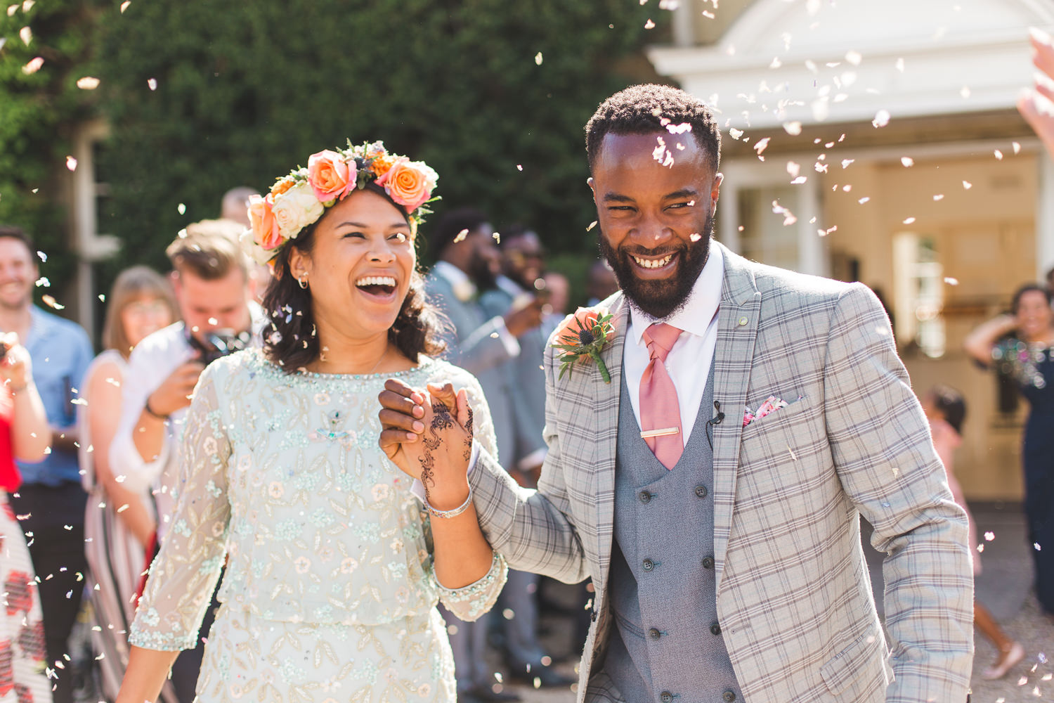 Bride and groom with confetti and beautiful fun faces at Northbrook Park wedding