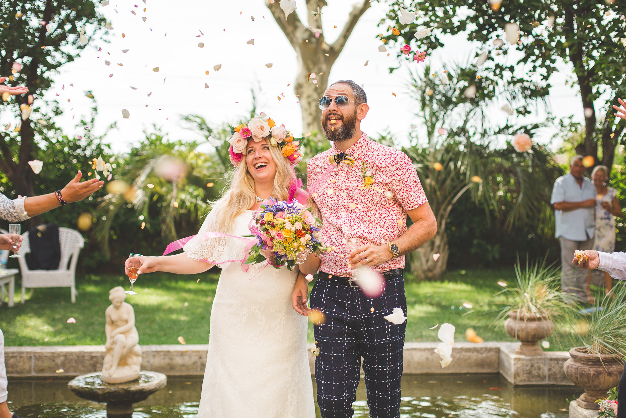 Destination wedding photography of bride and groom with colourful confetti in Chateau Du Puits Es Pratx. The bride also wears a colourful flower crown