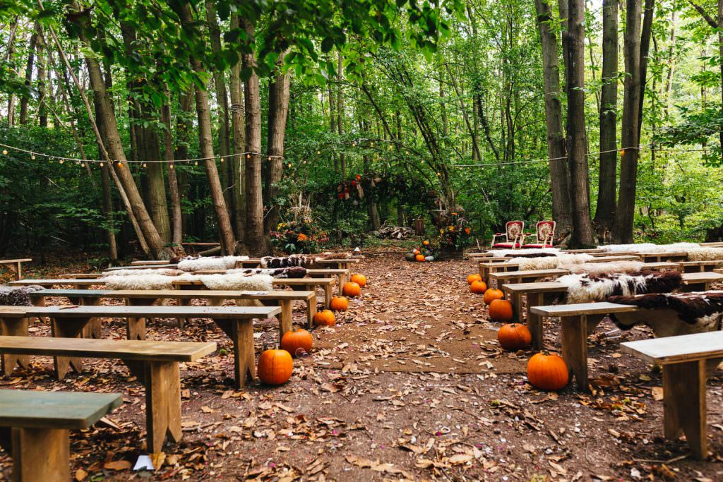 An autumnal ceremony set up in the woodlands during the dreys wedding photography, styled with pumpkins.