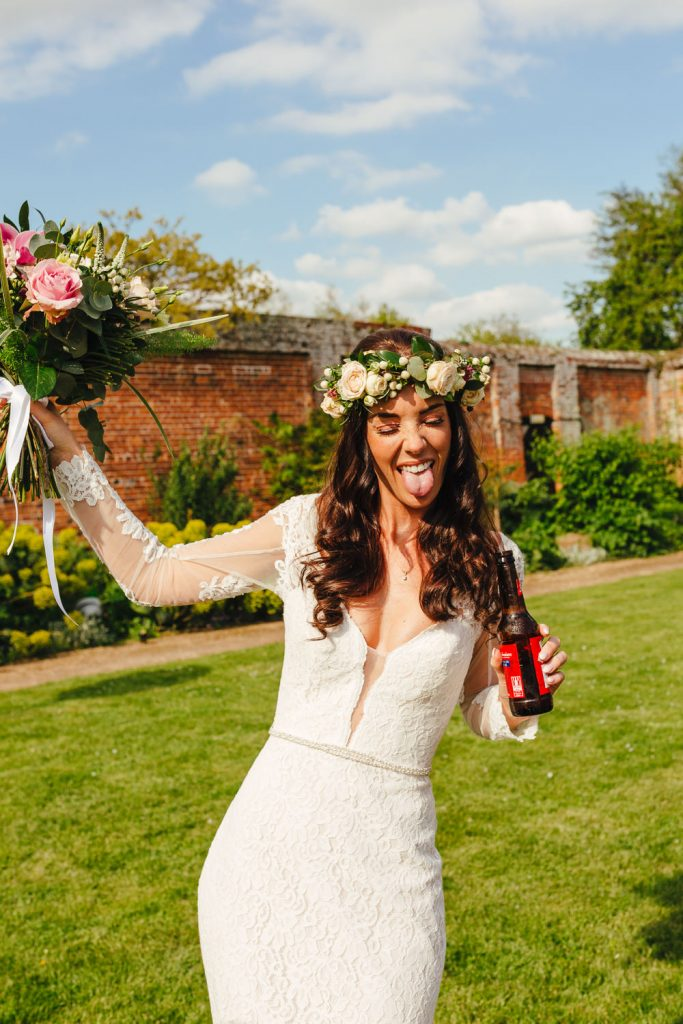 Bride drinking beer during her Quirky Alternative Festival Wedding Photography at Painshill Park