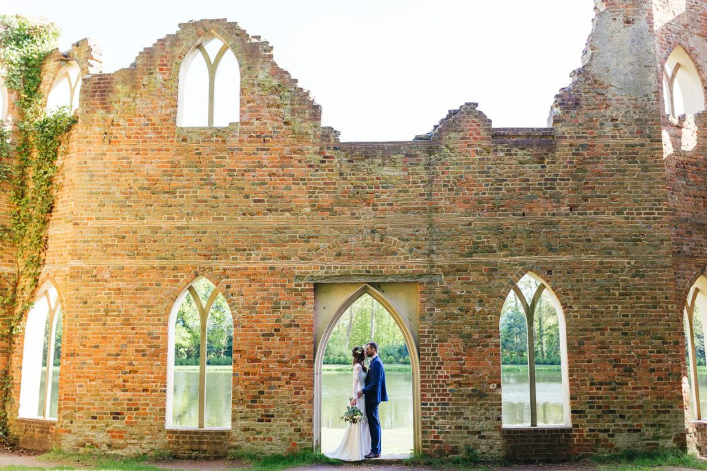 Couple infront of famous back drop which is Alternative Festival Wedding Photography at Painshill Park