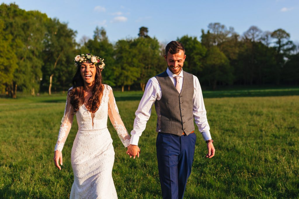 natural photo of couple laughing during Quirky Alternative Festival Wedding Photography at Painshill Park
