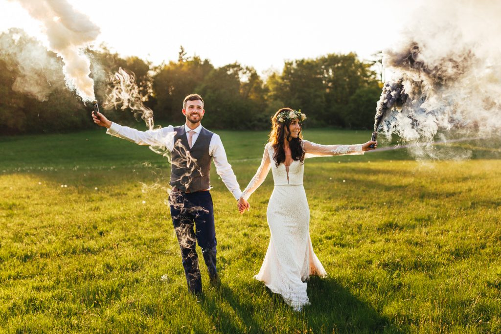 Bride and groom with smoke grenades during Quirky Alternative Festival Wedding Photography at Painshill Park
