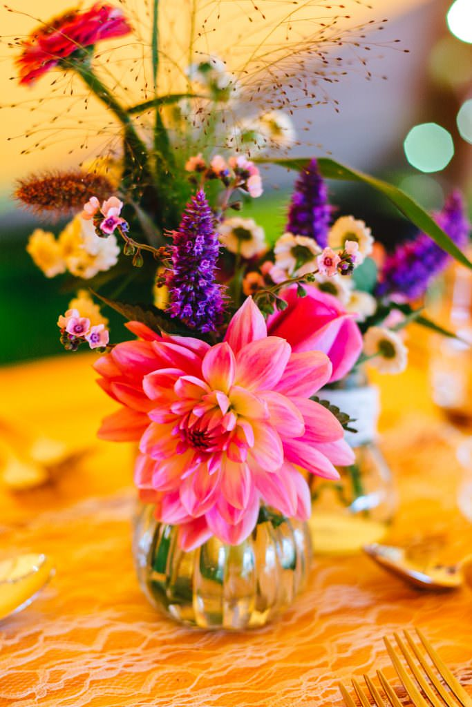 Bright coloured flowers inside the tipi during Colourful, Natural Festival Wedding Photography