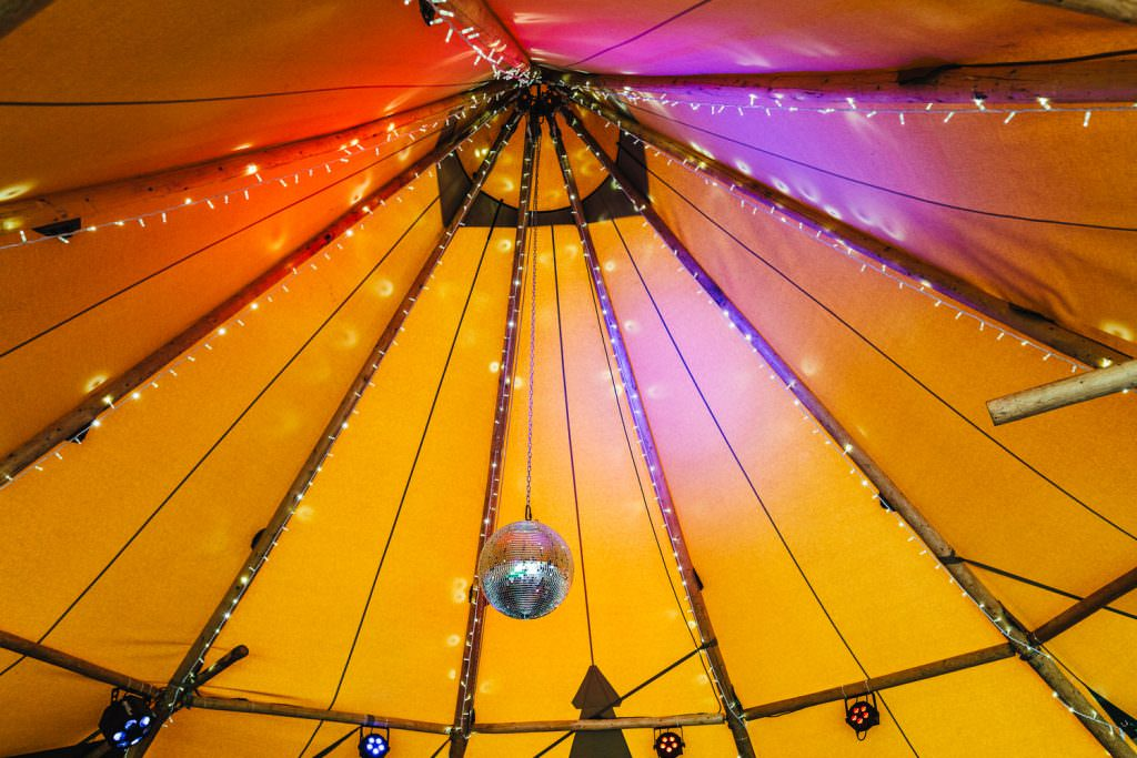 Inside tipi disco ball during Colourful, Natural Festival Wedding Photography