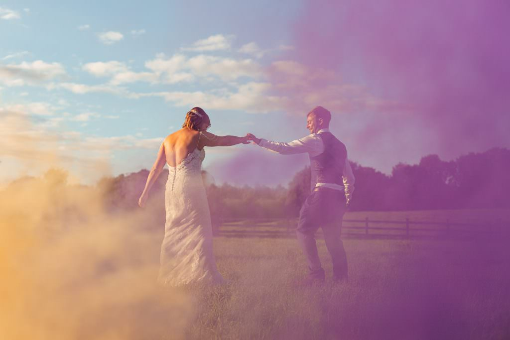 Bride and groom dancing with purple and yellow smoke bombs during Colourful, Natural Festival Wedding Photography