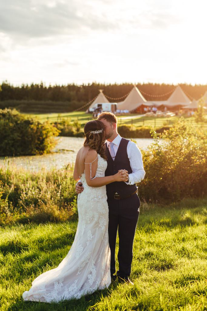 Couple in golden hour light with tipi in the background by the lake at bower hill farm. During Colourful, Natural Festival Wedding Photography