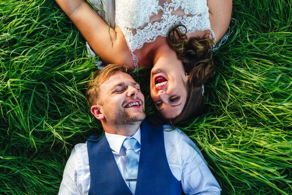 Couple laughing in grass during natural and relaxed wedding portraits. Colourful, Natural Festival Wedding Photography