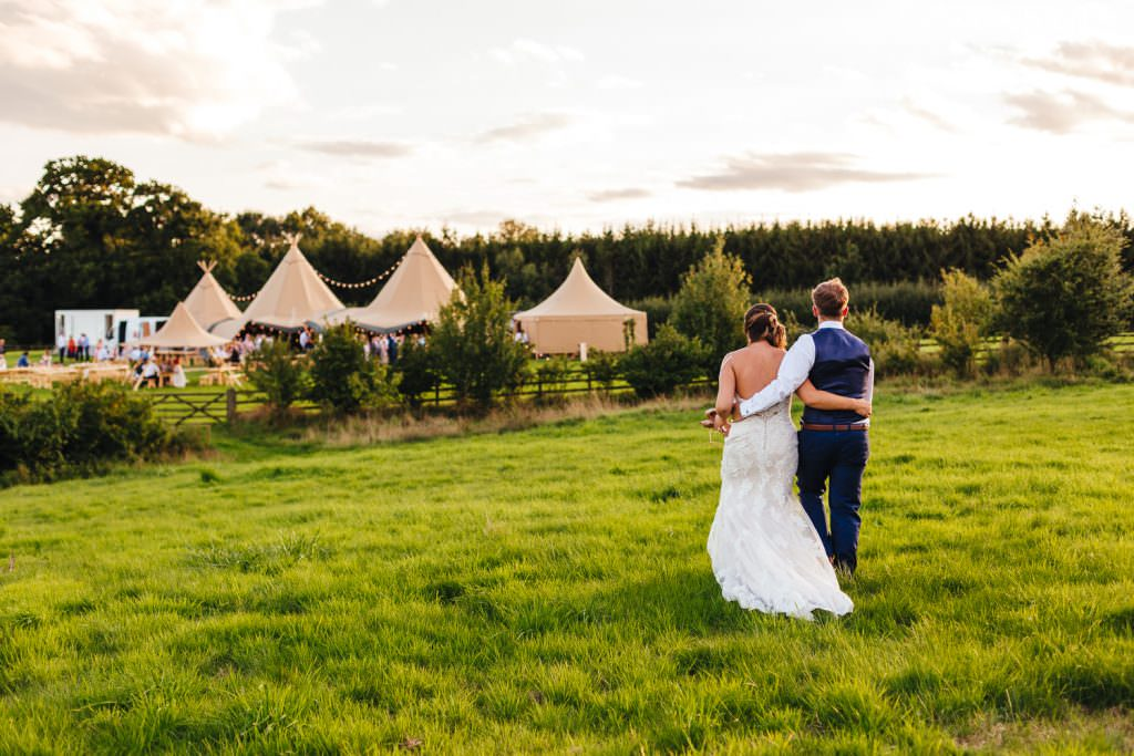 Bride and groom walking away with Tipi in the background at Bower Hill Farm. Colourful, Natural Festival Wedding Photography