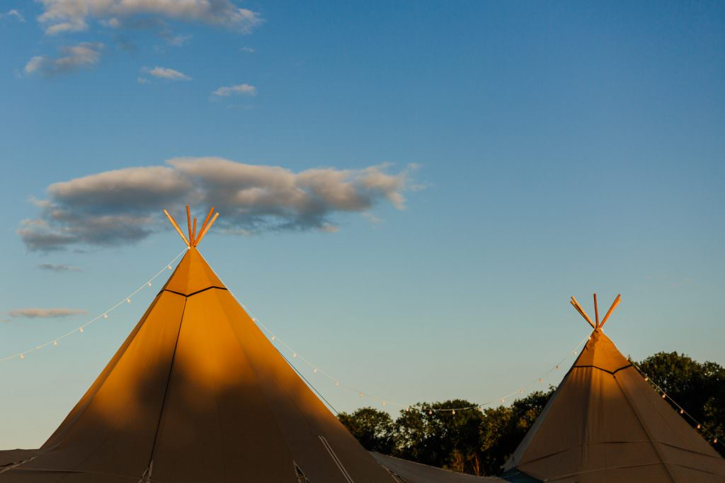 Tipi at Bower Hill Farm as the sun goes down. Colourful, Natural Festival Wedding Photography
