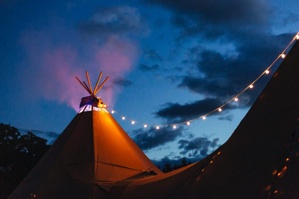 Coloured smoke coming out of the tipi as the sun goes down. Colourful, Natural Festival Wedding Photography