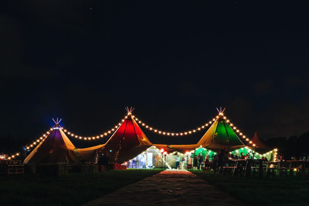 My Tipi event tipi at Bower Hill Farm lit up at night. During Colourful, Natural Festival Wedding Photography