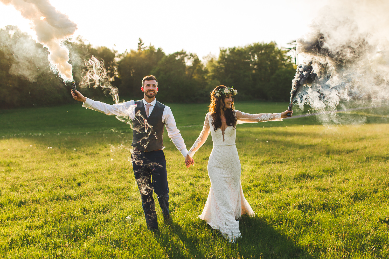 Bride and groom with smoke grenades laughing at painshill park. boho wedding vibes during Alternative Surrey Painshill Park Wedding Photography