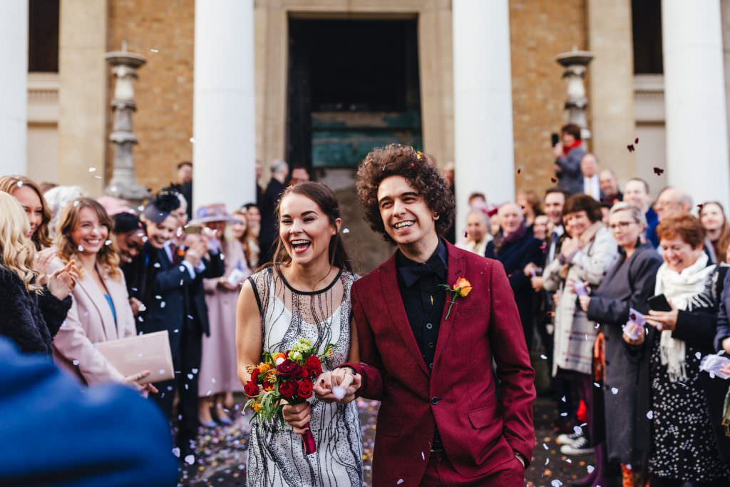 Happy smiles during confetti toss at london Asylum and Battersea Arts Centre Wedding