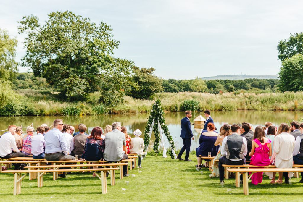 outside uk ceremony by lake at Rye Island Glastonbury Festival Themed West Sussex Wedding Photography