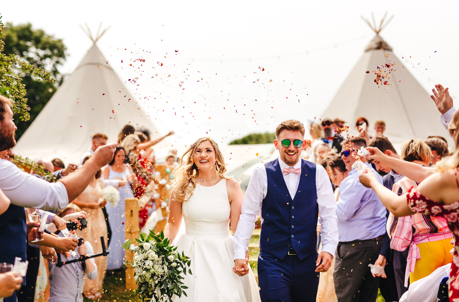 bride and groom smiling during confetti at Glastonbury Festival Themed West Sussex Wedding Photography infront of tipi