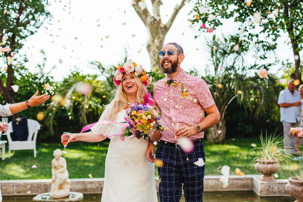 colourful festival wedding confetti with quirky couple. Bride wears Daughter of Simone wedding dress. Taken by South of France Destination Wedding Photography