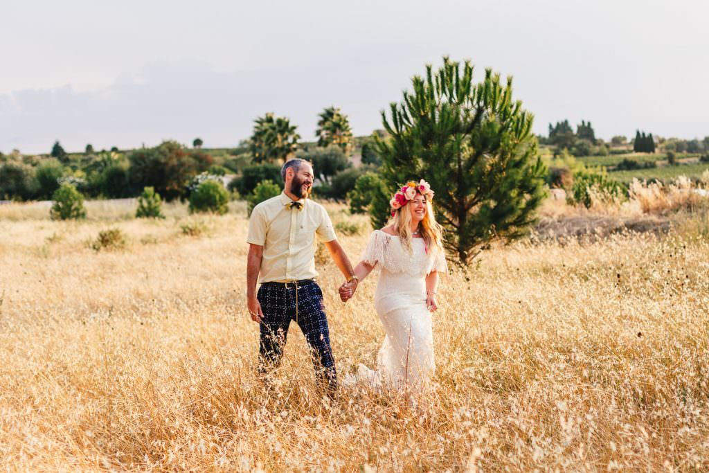 Couple walking in field of wheat in sunshine taken by South of France Destination Wedding Photographer at Chateau Du Puits Es Pratx