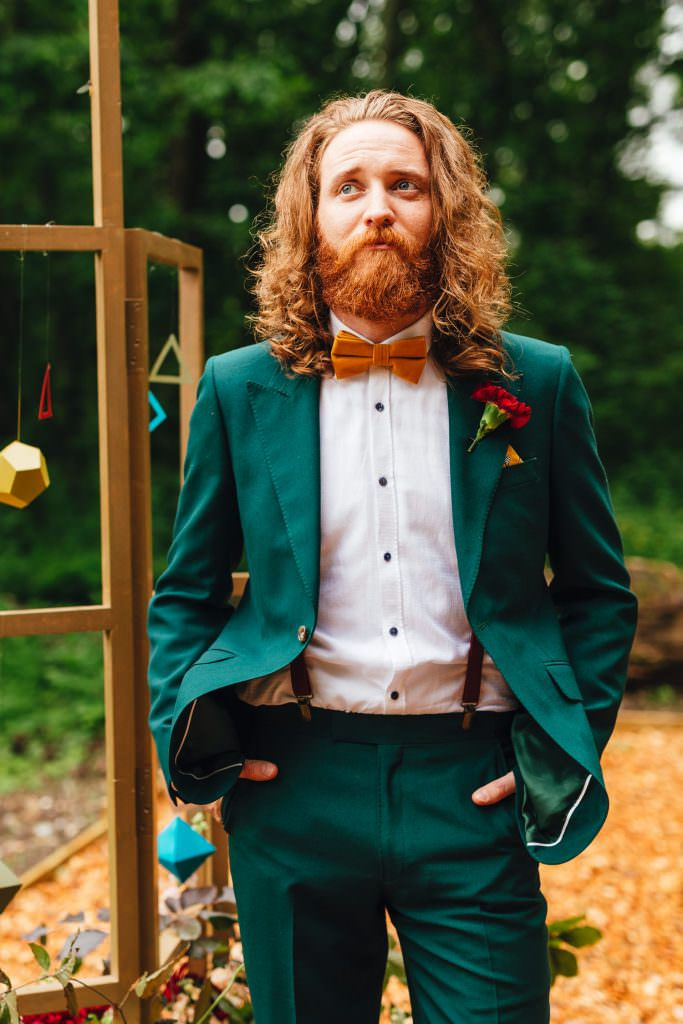 Portrait of a groom in a bottle green suit and mustard velvet tie during Wes anderson inspired wedding shoot