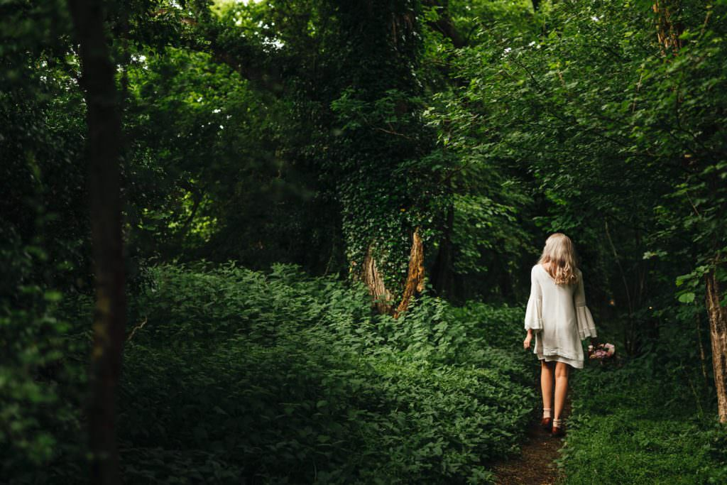 Bride in 70s indie brides mini wedding dress with bell sleeves in woodland during wes anderson inspired wedding shoot