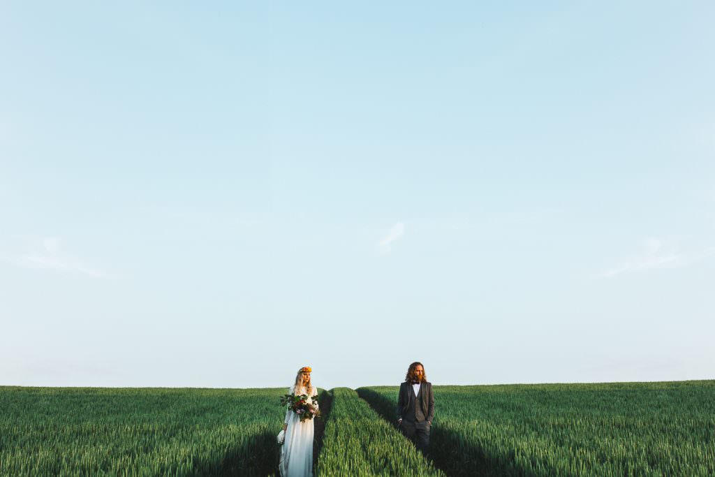 Bride and Groom in field of wheat during golden hour for a wes anderson inspired wedding