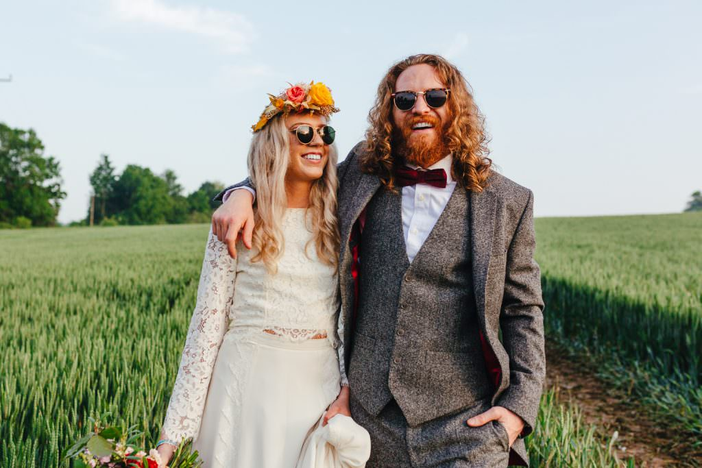 Bride and Groom in field of wheat during golden hour for a wes anderson inspired wedding, both wearing sunglasses, very cool quirky colourful wedding photographs