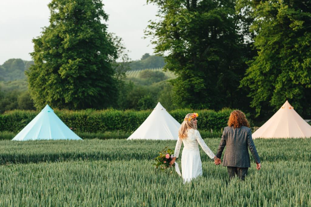 Bride and Groom in field of wheat during golden hour for a wes anderson inspired wedding with baylily camping tents in the backdrop