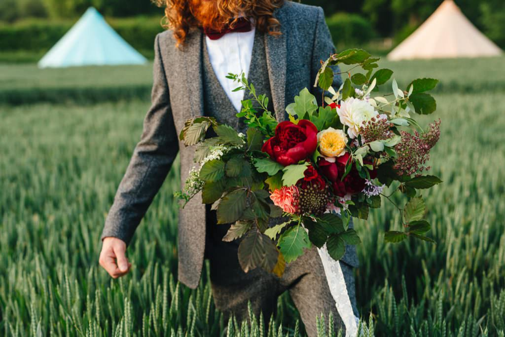 Groom in field of wheat during golden hour for a wes anderson inspired wedding