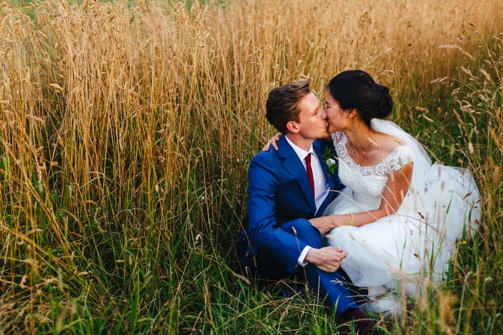 Bride and groom kiss in a field of wheat at golden hour during Cripps Stone Barn Wedding Photography portraits
