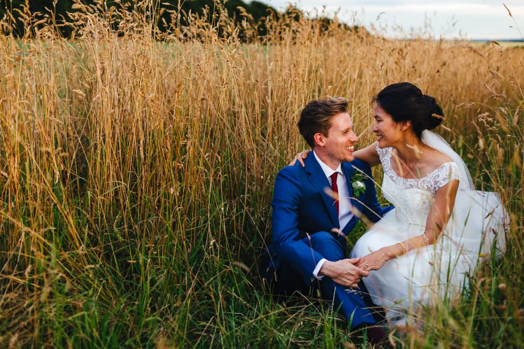 Bride and groom natural laugh in a field of wheat at golden hour during Cripps Stone Barn Wedding Photography portraits