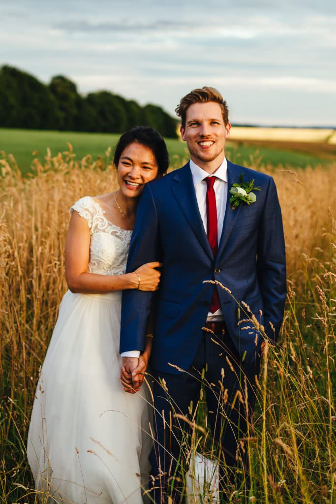 Couple embrace during Cripps Stone Barn Wedding Photography portraits. Moody skies and golden hour light in field of wheat. Bride Chinese and Groom English so a fusion wedding