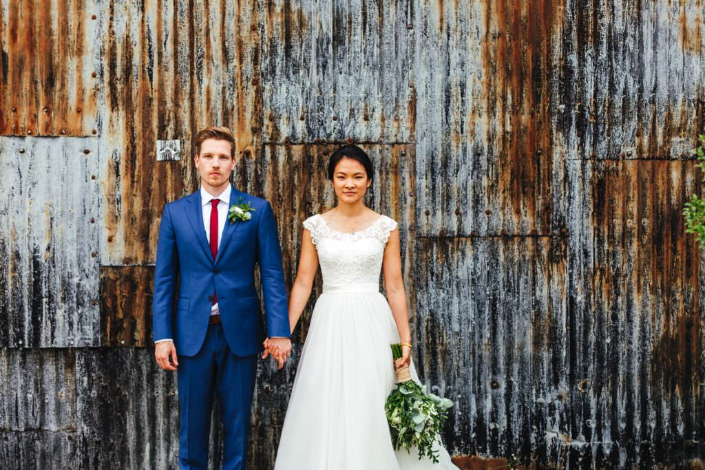 Bride and groom against metal grate wall at Cripps Stone Barn Wedding Photography.