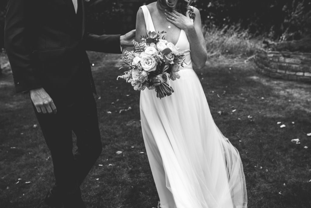 Black and white cropped image of bride and groom by Kirsty Mackenzie, a Fun creative hampshire wedding photographer