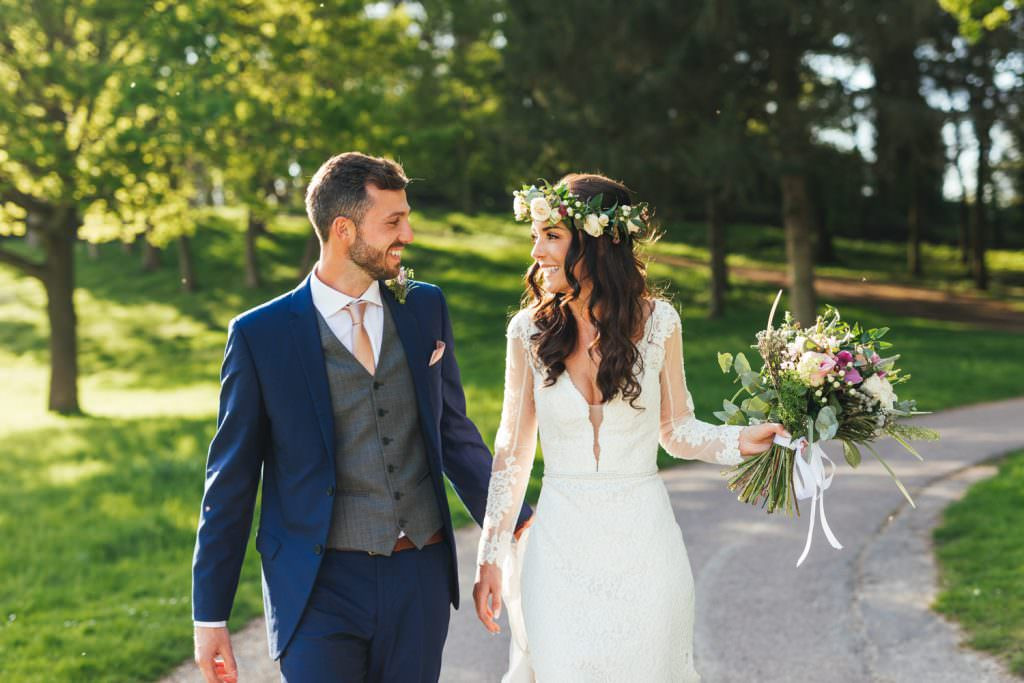 boho couple with bride wearing flower crown walking in the sunshine and holding hands, captured by Fun creative hampshire wedding photographer