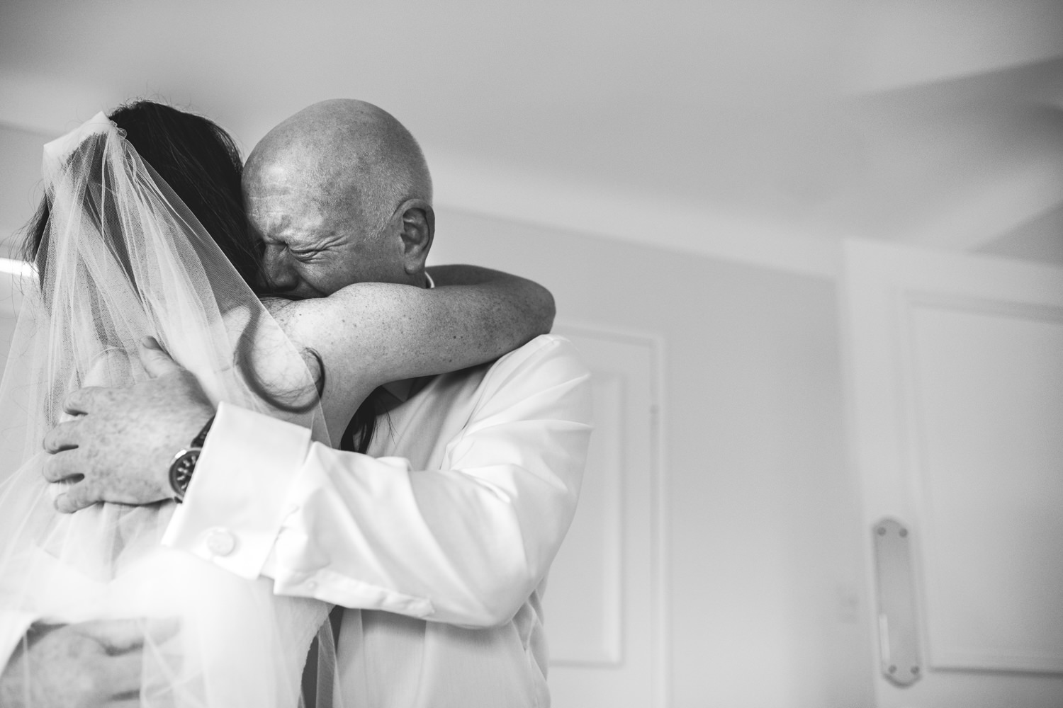 Image of father seeing his daughter in a wedding dress for the first time. Very emotion and natural image by Fun creative hampshire wedding photographer