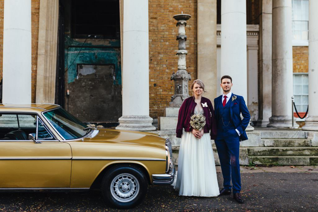 Bride and groom with gold vintage car outside a Christmas Inspired Winter Wedding at the Asylum