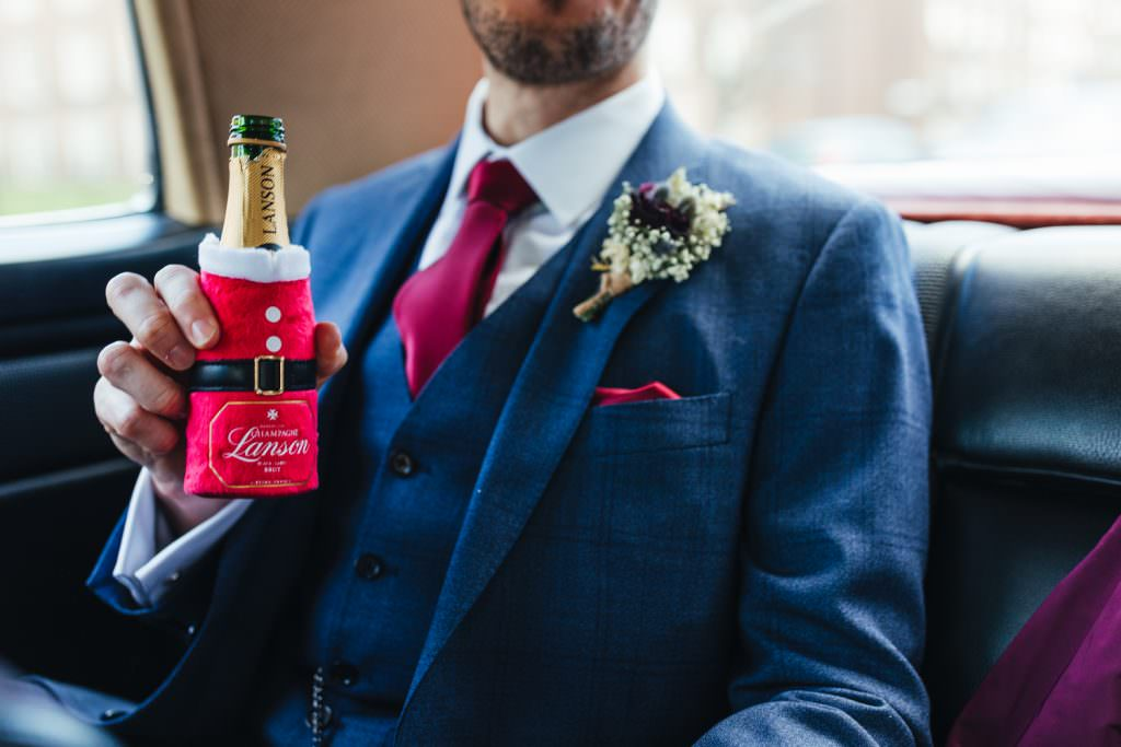 Groom holding Christmas inspired Lanson at Christmas Inspired Winter Wedding at the Asylum