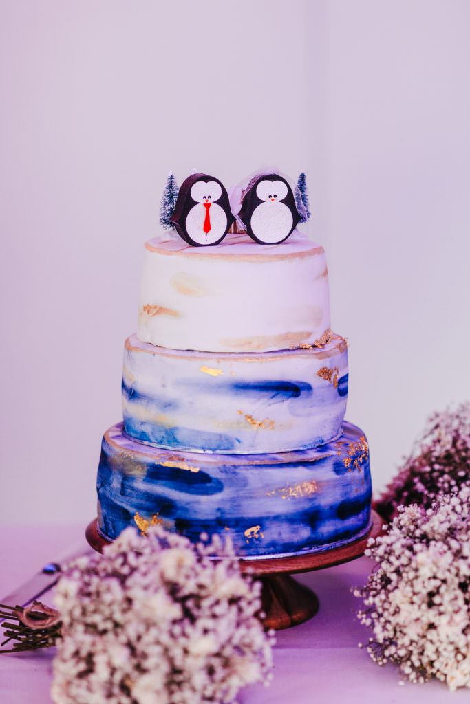 Cute Christmas inspired wedding cake with penguins on during Christmas Inspired Winter Wedding at the Asylum