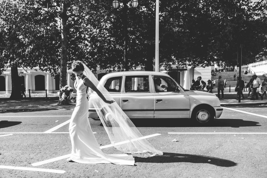 Bride walking along in made with love dress with veil and black London cab taxi during Stylish Fun & Natural Institute of Contemporary Arts Wedding Photography