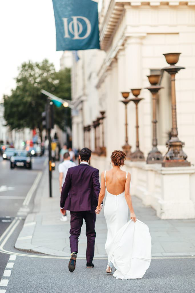 Bride and groom walking along London Pall Mall during Stylish Fun & Natural Institute of Contemporary Arts Wedding Photography. Bride wears Made with love and groom is in a purple beggars run suit