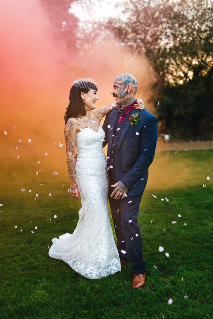 Alternative tattooed couple having wedding portraits with smoke bombs during Vintage Rockabilly meets Peaky Blinders Inspired Wedding in Hertfordshire
