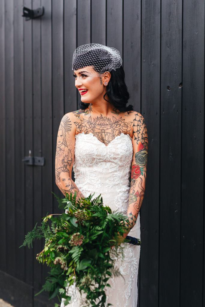Alternative vintage tattooed bride in wedding dress during Vintage Rockabilly meets Peaky Blinders Inspired Wedding in Hertfordshire