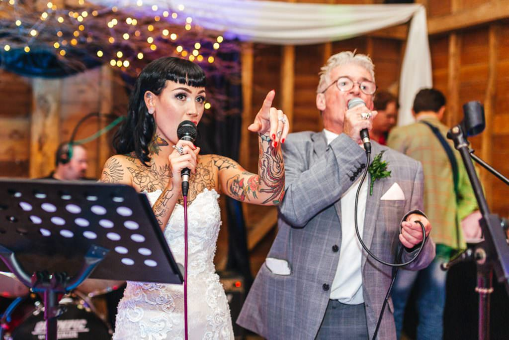 Tattooed bride gets up and sings during Vintage Rockabilly meets Peaky Blinders Inspired Wedding in Hertfordshire