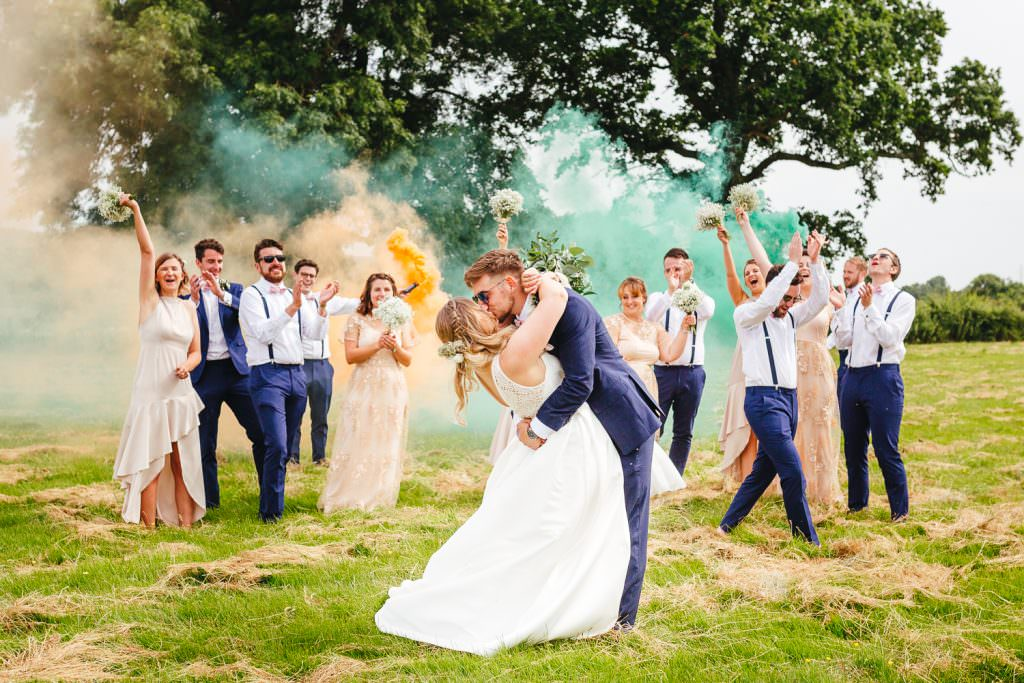 Wedding squad goals with wedding party cheering with smoke bombs taken by fun natural Sussex wedding photographer.