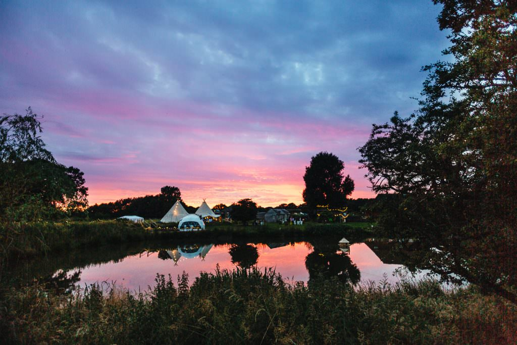 Tipi by a lake and coloured sky at Rye Island wedding taken by fun natural Sussex wedding photographer.