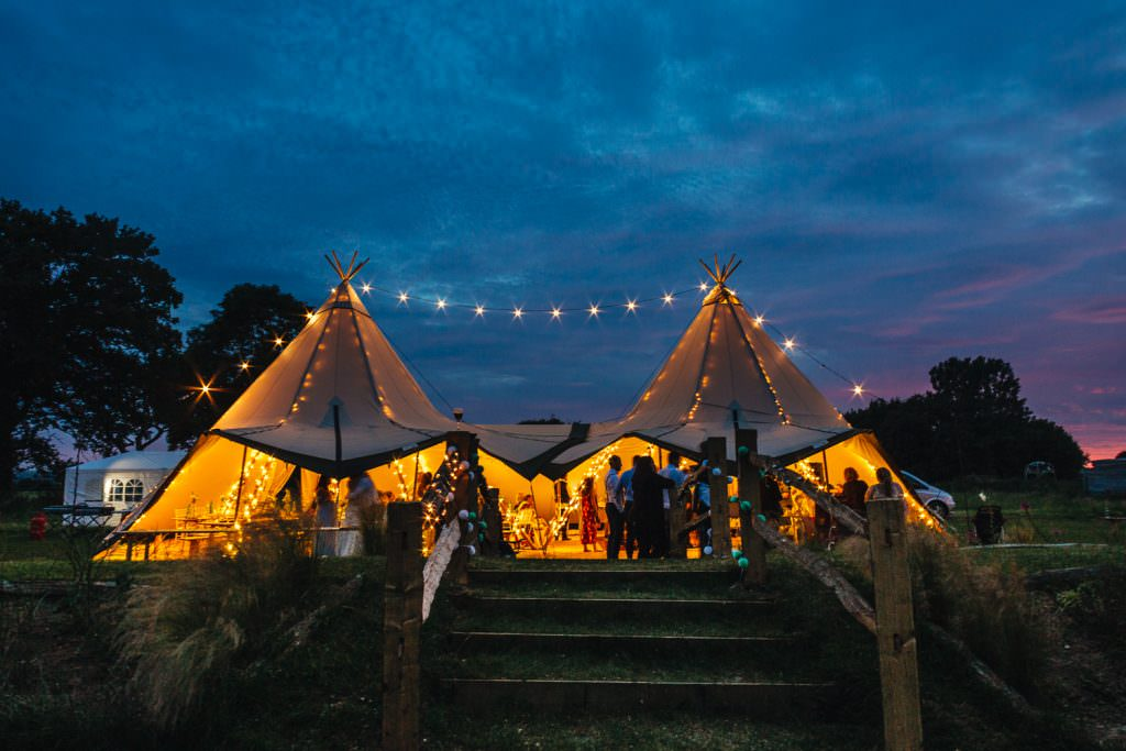 Tipi at night all lit up during festival wedding at Rye Island taken by fun natural Sussex wedding photographer.